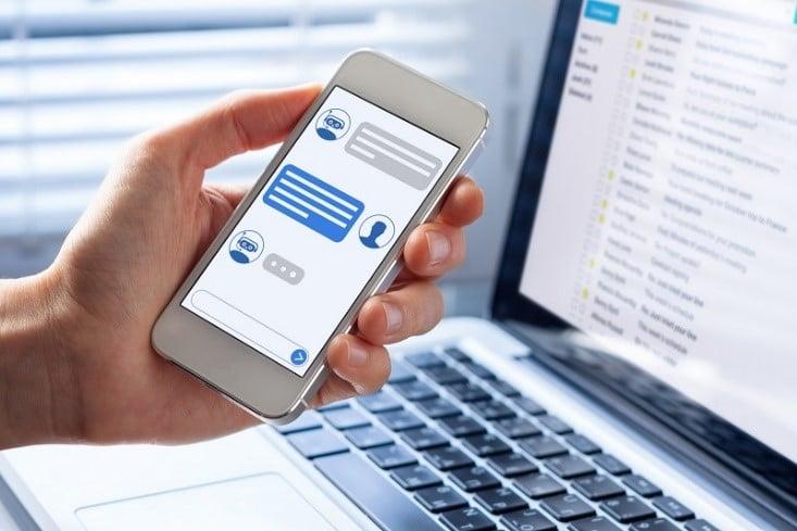 Foto de uma mão segurando um celular em um app de bate-papo e um notebook com um programa de email aberto